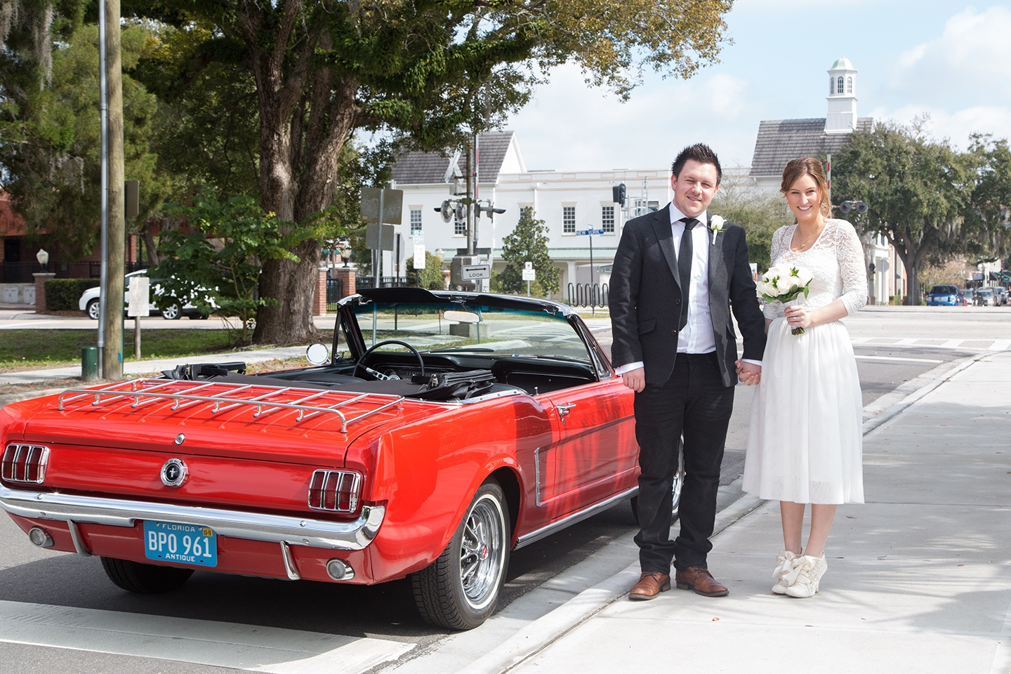 Driving away from their Orlando wedding in style in a bright red Ford Mustang!