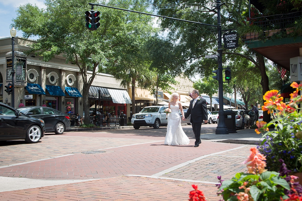 A bride and groom walking through historic Winter Park