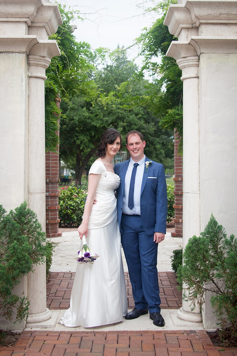 A happy UK couple posing alongside the garden after their Central Florida wedding.