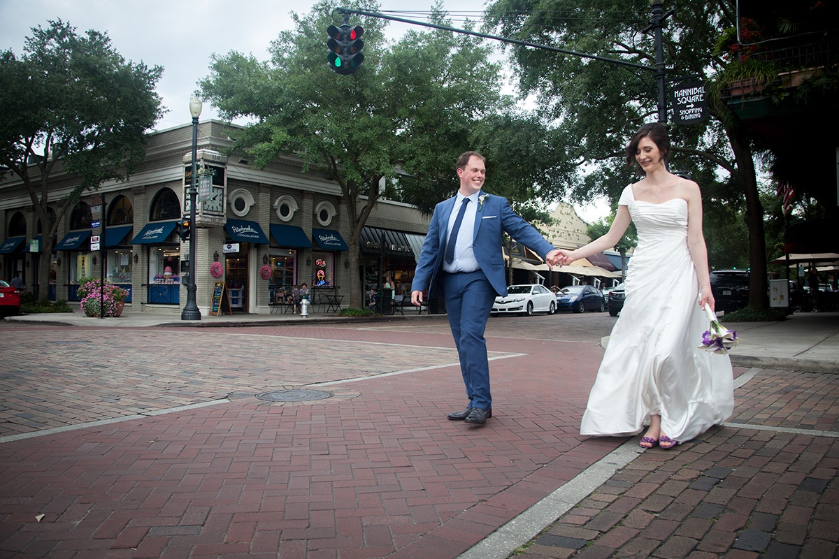 A bride and groom walk through the streets of historic Winter Park.
